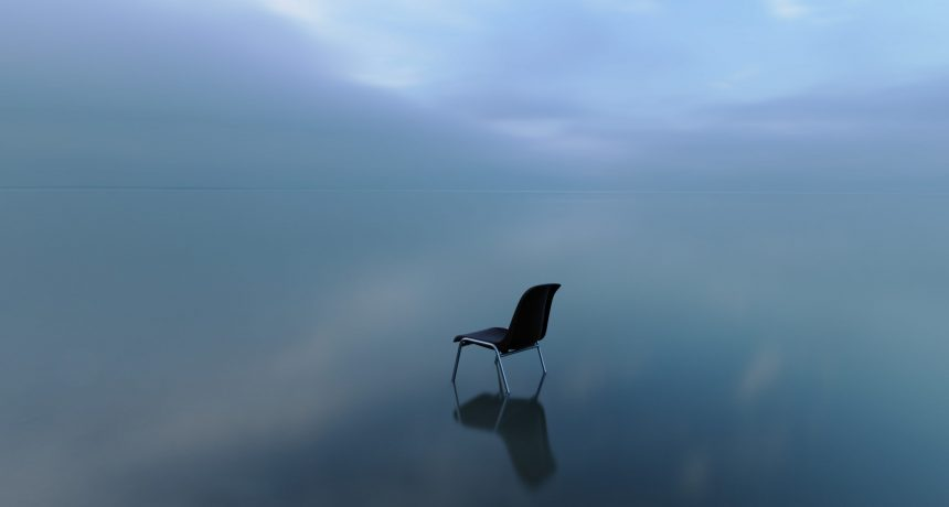 A single chair reflecting on a water surface on a stormy day